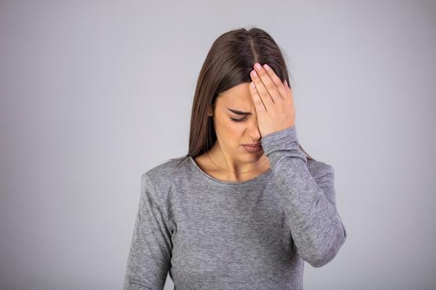 젊은 여자는 눈에 통증이 있습니다. 회색 배경에 눈의 통증과 젊은 여자.