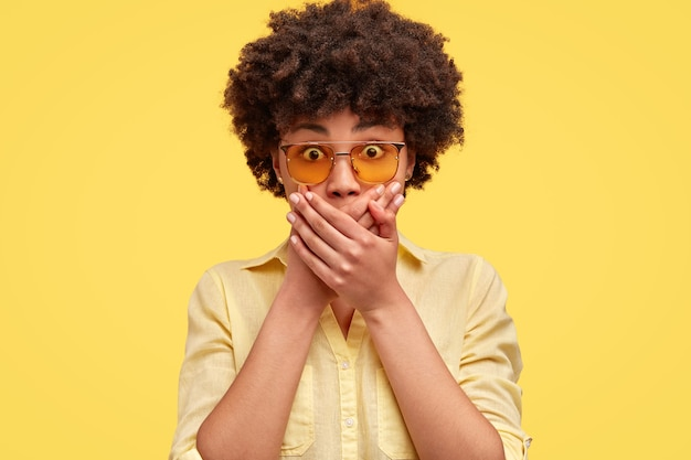 Young woman has scared expression, covers mouth with hands, looks in astonishment, wears trendy shades and blouse