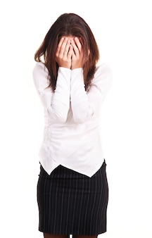 Young woman has shut face with hands, isolated on white