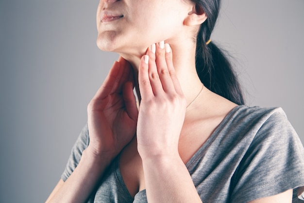 A young woman has a sore throat on a gray