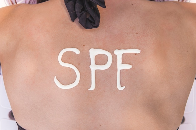若い女性はビーチで日焼け止めクリームで作られた彼女の背中にspfの言葉を持っています。日焼け防止係数の概念。閉じる