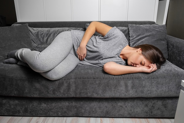 Young woman has a stomachache lay on the sofa