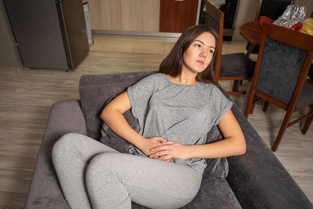 Young woman has a stomachache, top view