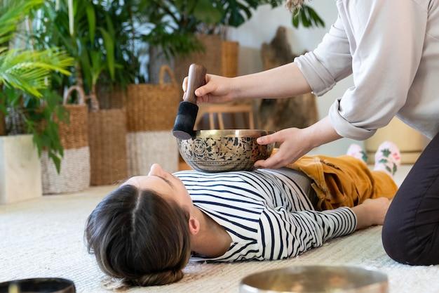 젊은 여자는 집에서 전통적인 티베트 청동 심벌즈와 티베트 마사지 노래 그릇 치료를 가지고