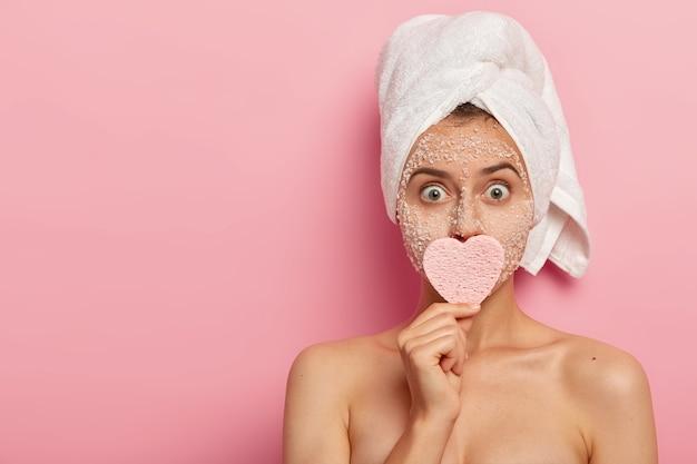 La giovane donna ha gli occhi ben aperti, si sente scioccata, riduce la secchezza della pelle con una maschera nutriente naturale, tiene la spugna cosmetica sulla bocca, è impegnata con la routine di cura della pelle
