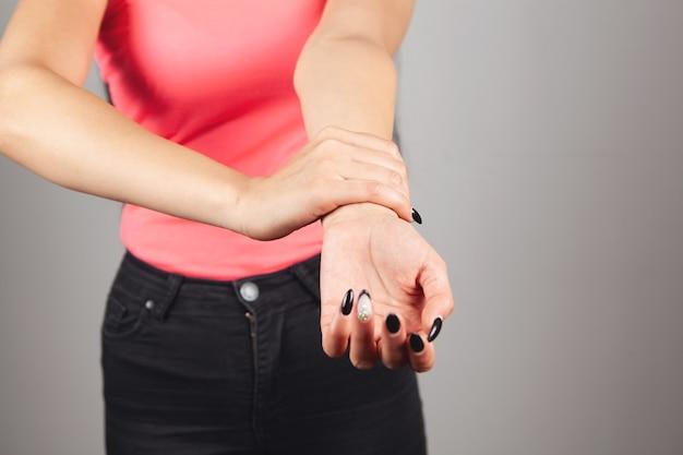 若い女性は手首の痛みがあります