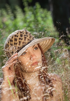 Young woman in a hat among the grass illuminated by the rays of the sun on a forest background