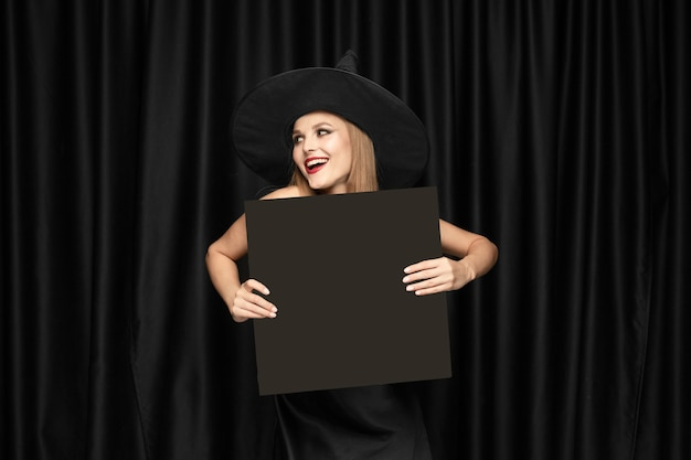 Young woman in hat as a witch holding black board against black curtains