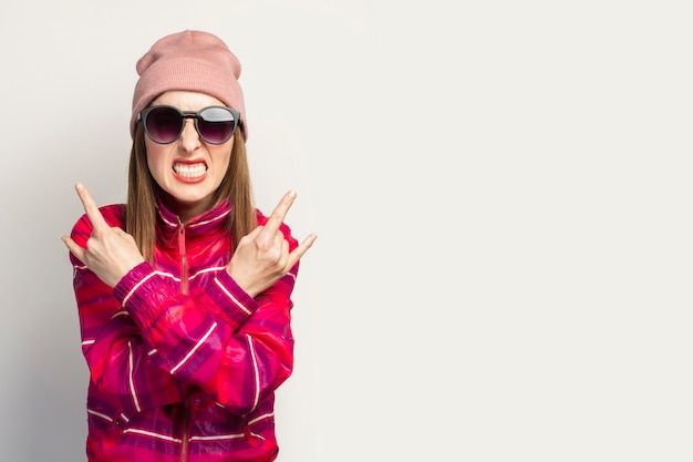 Young woman in a hat and glasses and a pink sports jacket makes a rock and roll goat gesture.