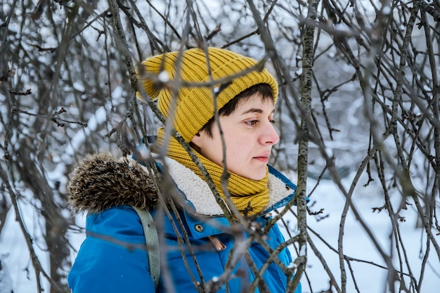 Young woman in hat and jacket among branches of trees in winter park.