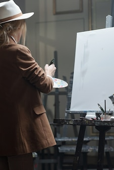 Young woman in hat and jacket mixing colors on palette while standing in front of easel with blank paper and going to paint