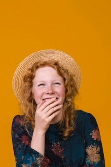 Young woman in hat laughing and covering mouth