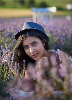 Young woman in hat lying in lavender field on summer day