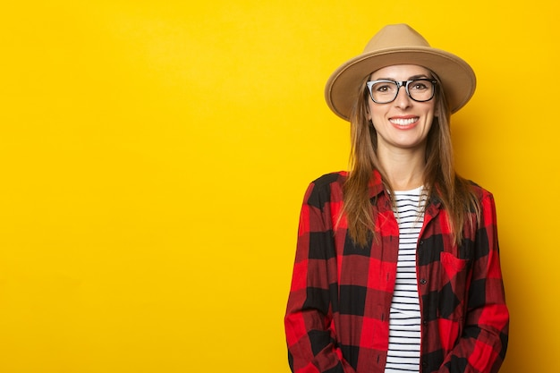 Young woman in hat and plaid shirt on yellow.