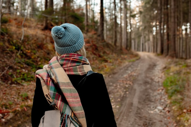 Young woman in hat and scarf walking in a forest