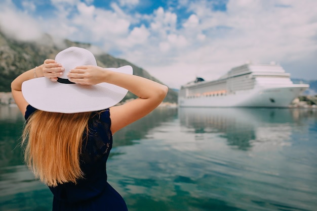 Young woman in hat stands on cruise liner background, rear view