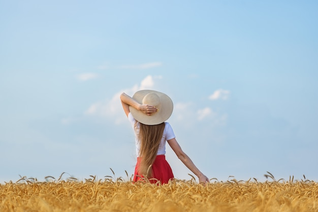 Young woman in hat stands in wheat field on blue sky background. weekend outdoors