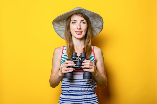 Young woman in a hat and a striped dress holds binoculars on a yellow space.