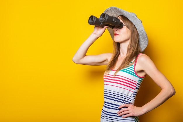 Young woman in hat and striped dress looks through binoculars on a yellow space.