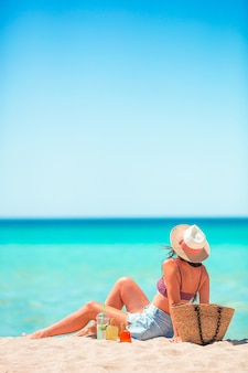 Young woman in hat sunbathing on the beach