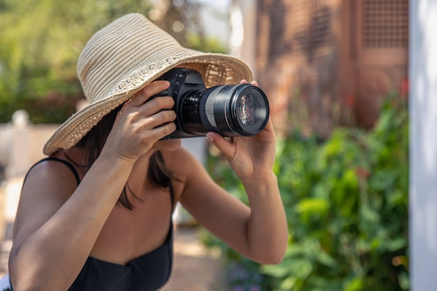 A young woman in a hat takes pictures with a professional slr camera on a hot summer day