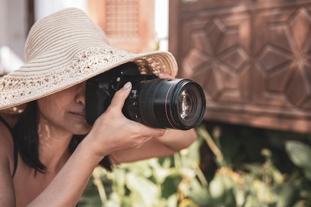 A young woman in a hat takes pictures with a professional slr camera on a hot summer day.