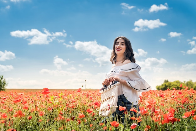 Young woman in hat walk at poppy field pick flowers. summer time