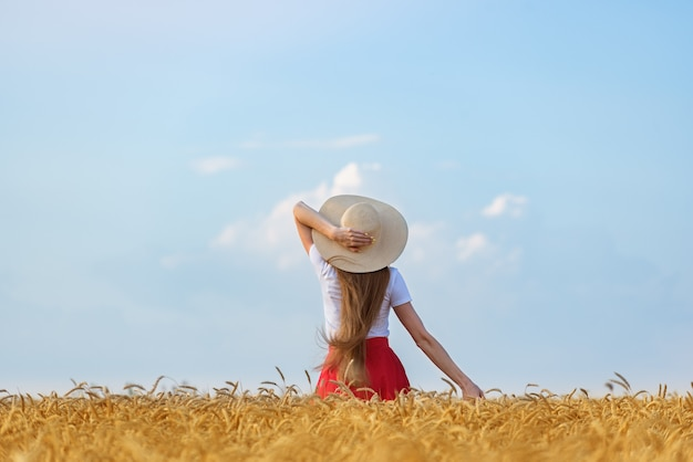 Young woman in hat on wheat field and sky background. freedom relax a naturalness