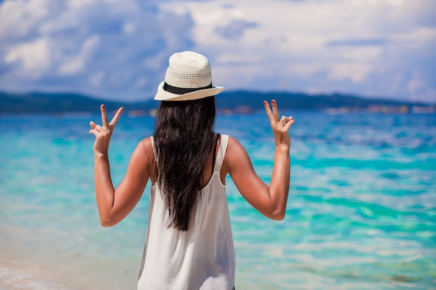 Young woman in hat with raised hands at perfect beach