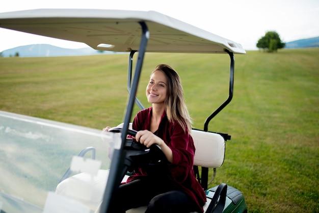 젊은 여자는 산의 필드에 골프 버기 자동차와 재미를