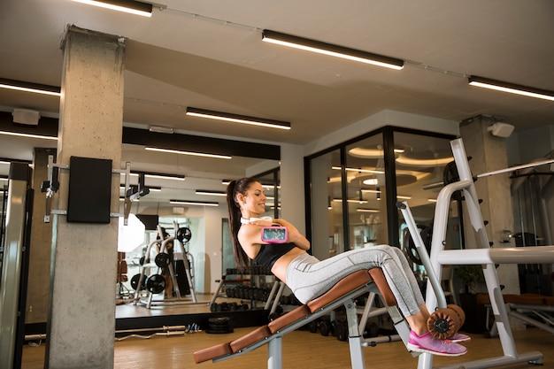 若い女性はジムのベンチに座るでトレーニングを持っています