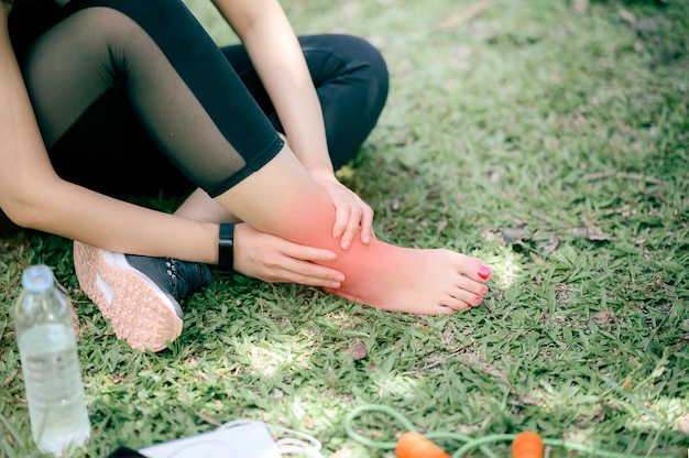 Young  woman have a ankle pain after running outdoors, copy space.