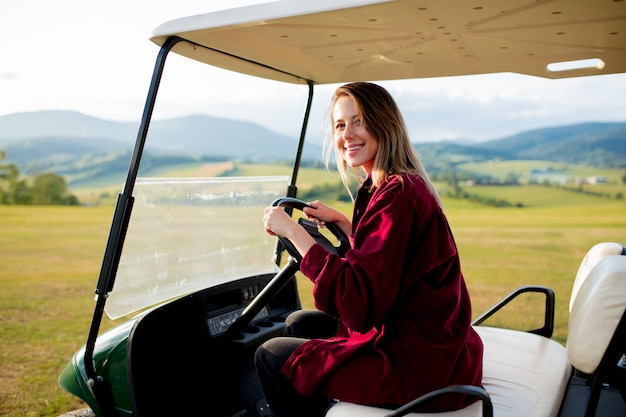 Young woman have a fun with golf buggy car on a field in mountains