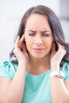 젊은 여성은 두통 편두통 스트레스나 이명을 앓고 있습니다. 그녀의 귀에서 휘파람 소리가 납니다.