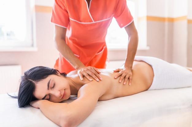 若い女性は、医学的回復マッサージを受けています。
