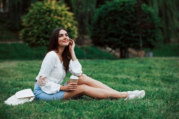 Молодая женщина имеет выходные и сидит в парке в дневное время