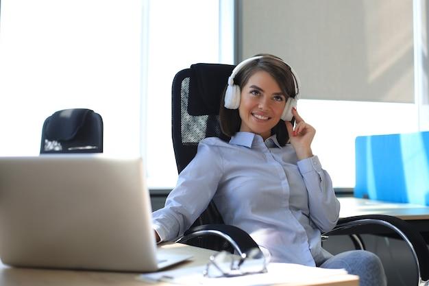 休憩を取り、職場に座ってヘッドフォンで音楽を聴いている若い女性。