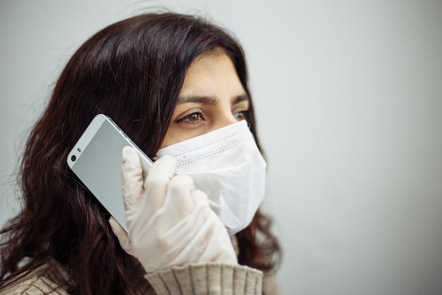 コロナウイルスパンデミックのために検疫中に自宅で仕事をしている携帯電話に電話をかけている若い女性。美しい少女は、医療用マスクと手袋を着用し、電話でビジネスについて話し合って家にいます。