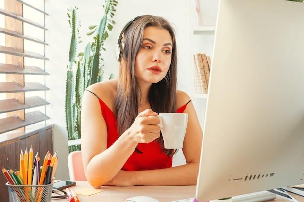 Молодая женщина, перерыв на кофе, сидя в своем офисе