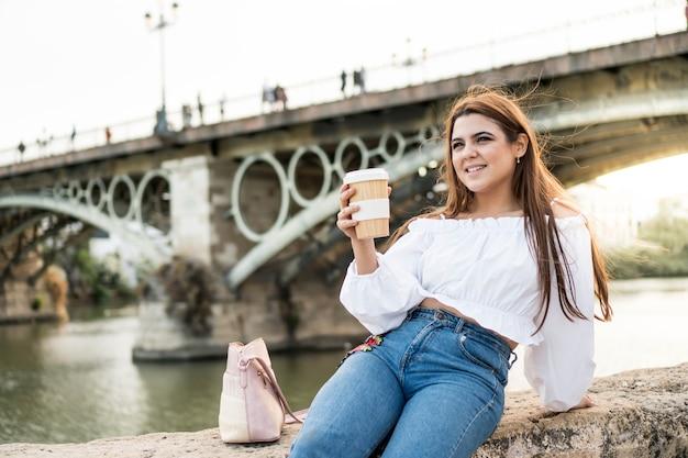 セビリアスペインの川のそばに座ってコーヒーを飲んでいる若い女性夏を楽しんでいる笑顔の女の子