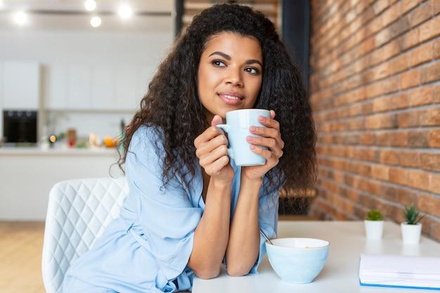 一杯のコーヒーを持っている若い女性