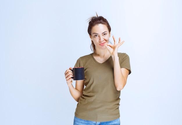 Молодая женщина с чашкой напитка и наслаждаясь вкусом