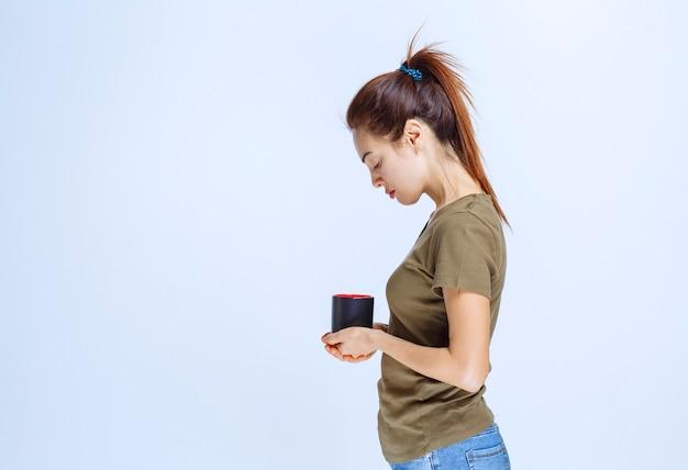 Молодая женщина с чашкой напитка утром