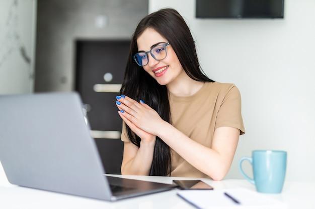부엌에서 노트북을 사용하면서 차 한 잔을 마시는 젊은 여성