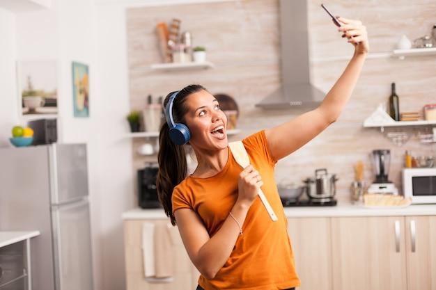 良い一日を過ごして、台所でselfieを取る若い女性