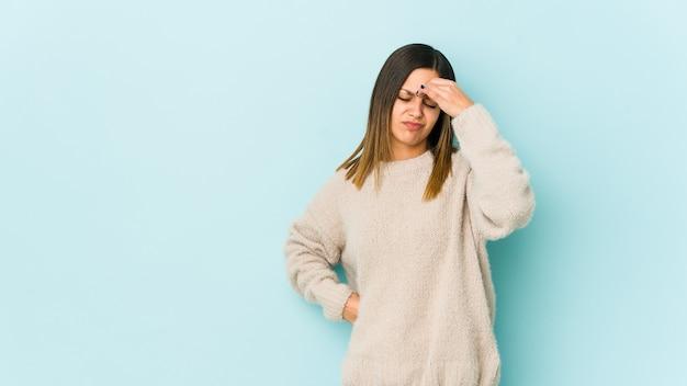 Молодая женщина, имеющая головную боль, касаясь передней части лица.