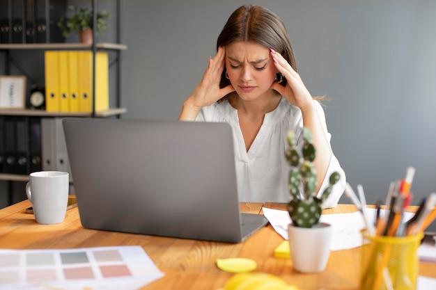 Молодая женщина, имеющая головную боль на работе