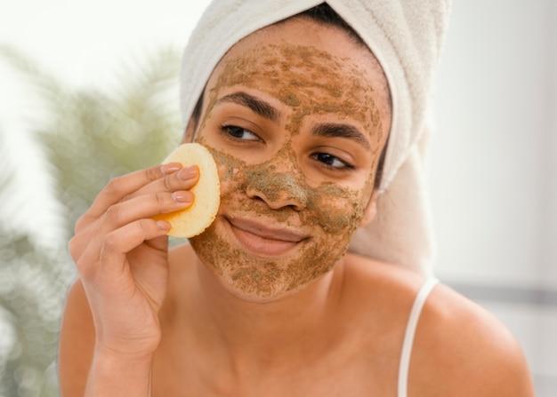 Молодая женщина с домашней маской на лице
