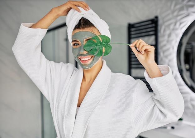 彼女の顔に自然なマスクを持っている若い女性