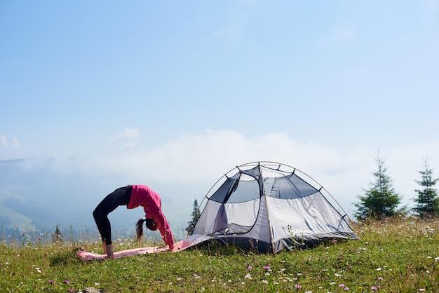 산에서 여름 아침에 관광 텐트 근처에서 휴식을 갖는 젊은 여자